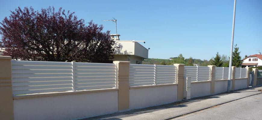 Clôture aluminium blanche posée entre piliers béton